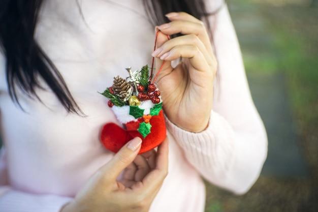 クリスマスの装飾、ブートとリボンを保持して女性の手を閉じます。