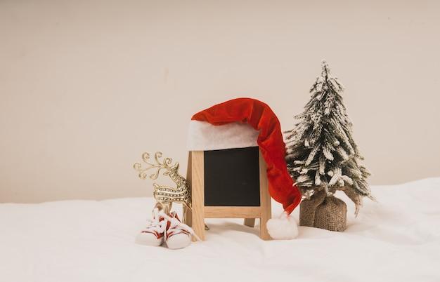 白い背景に黒板とクリスマス休日の装飾。