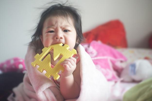 小さなアジアの女の子が色のおもちゃをかみます。
