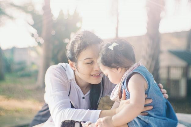 アジアの赤ちゃん女の子が母親の支援を得て公園で遊んでいます。