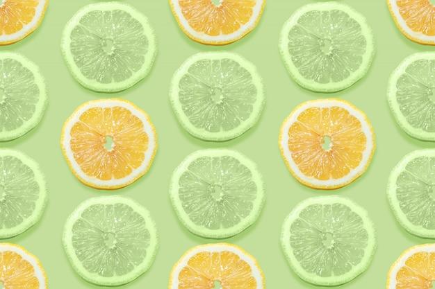 緑のパステル調の抽象的な背景にレモンスライスとフルーツのシームレスなパターン。