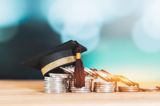 木製テーブルの色の背景にコインの上のスタックにお祝いの卒業生