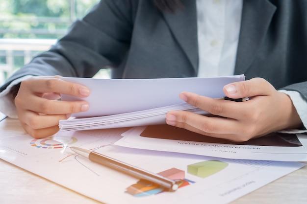 Руки молодых женщин бизнес-менеджеров, проверка и оформление стопку документов