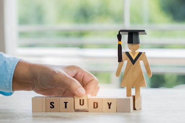 Студенческая рука, размещающая деревянный домино домино с письмом исследование возле знака древесины выпускной