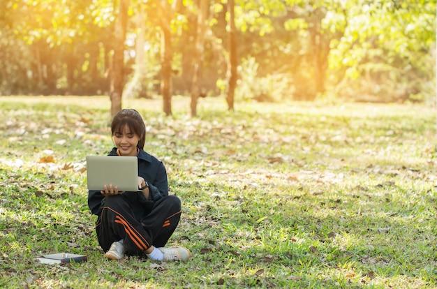 教育学習勉強コンセプト:魅力的な幸せなアジアの若い女の子が検索を楽しむ