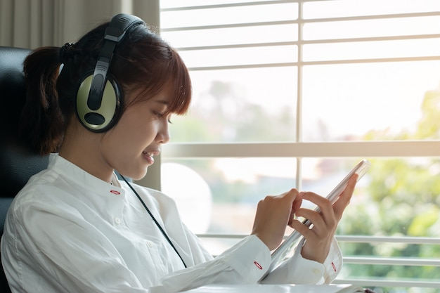 学生学習のオンライン学習の概念:ヘッドフォンで聴く美しいアジアの女の子