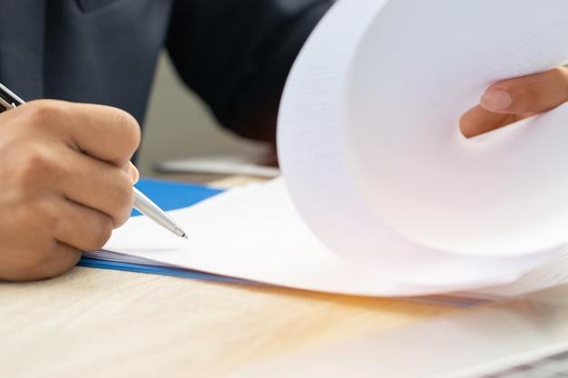 Азиатский бизнесмен менеджер по проверке и подписанию документов, заполняющих документы