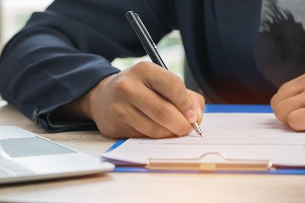 アジアビジネスマンマネージャーチェックし、申込者の記入書類に署名するレポート会社
