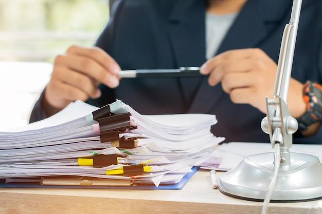 アジアビジネスマンマネージャー座っている申請書に署名するためのペンを保持する書類を報告する