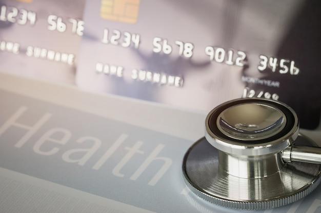 病院の机のカードホルダーに番号を持つクレジットカードのモックアップに聴診器。健康保険