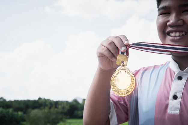アジアの少年の勝者の手がメダルを獲得しました競争概念の賞