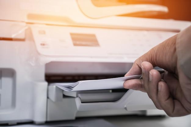 忙しい仕事机のオフィスにレーザープリンターで紙のプロセスプレスで働く実業家の手