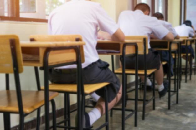 教育のための試験の背後にある複数の選択肢のクイズのための鉛筆で試験をテストする制服学生
