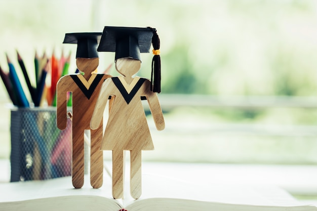 Снова в школу, два человека подписывают древесину с выпускной, празднующей кепку на открытом учебнике