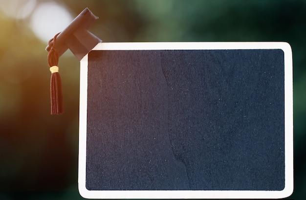 空のチョークまたはテキストの木製フレームのバックボード上のバナーデザイン卒業教育キャップ