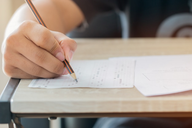 男の手の高校、試験のための鉛筆を保持している大学生
