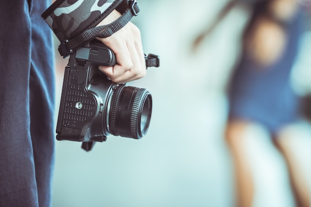 写真を撮る準備ができてのスマートな女性の手でデジタル一眼レフカメラでプロの写真家の風景、写真家はイベント、ビンテージトーンを覚えて喜びのためにスナップショットを取ります