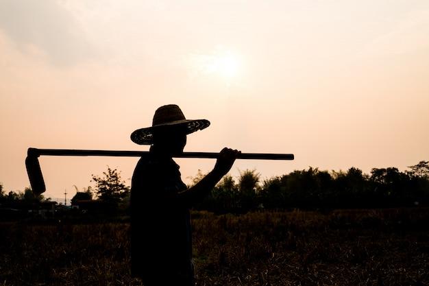 農業農家生活概念:スペードを保持している労働者または庭師の黒いシルエットが夕日の光で土を掘っています。