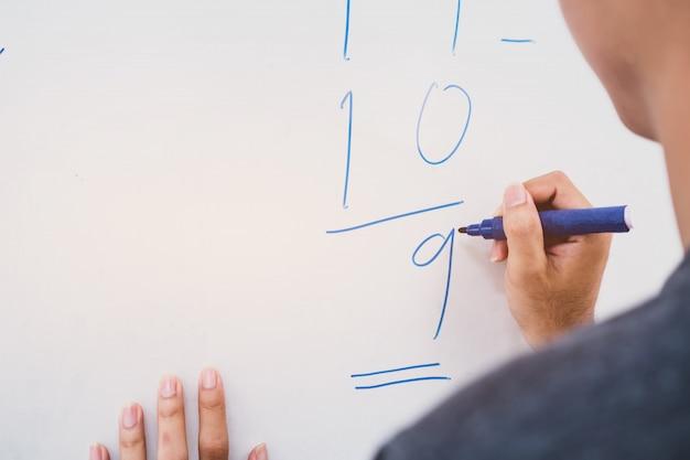 解加算和と減算を解くアジアの少年の背面図