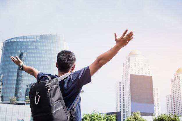 Вид сзади молодого человека азиатского туриста рюкзаком, стоя на улице с распростертыми объятиями для свободы