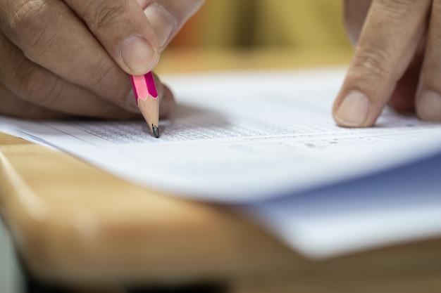 Руки студента, держа перо для тестирования экзаменов, написание листа ответов
