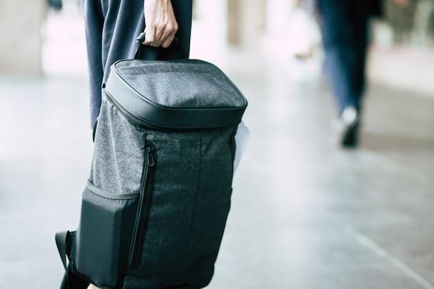 バックパッカーを保持している若い男旅行者のクローズアップ