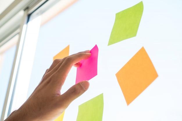 ビジネス人々の手がオフィスで会議のためのガラスリマインダースケジュールボードに付箋紙を投稿します。