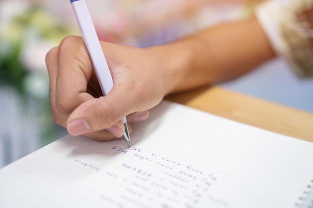 男子学生の宿題のために大学で図書館のペンでノートにメモを書くと書く