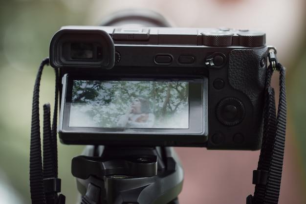 カメラマンの背後にあるアジアの美しさのブロガーレビュースマートフォンチュートリアル