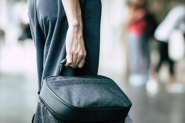 屋外都市のターミナルでバックパッカーやブリーフケースを待っているバスを保持している若い男旅行者のクローズアップ