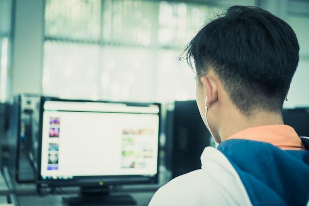 Вид сзади азиатский студент мужской инженер, использующий компьютер для поиска информационных данных в интернете