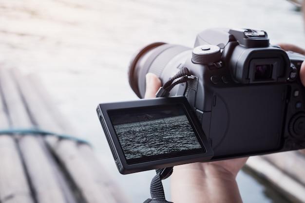 カメラマンは写真を撮るカメラの記録のための三脚にビデオカメラやプロのデジタル一眼レフを設定