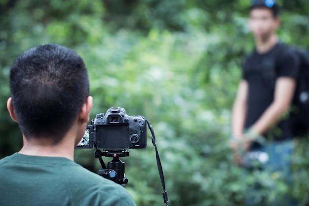若いアジアのカメラマンがビデオカメラのインタビューやプロのデジタルミラーを三脚にセットしない