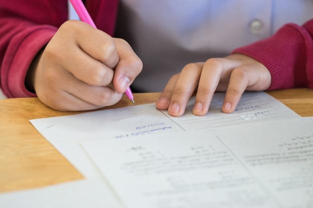 高校、アジアの試験室、テストまたは試験の白い解答用紙に情報を書くペンを使用している学生は、知識、スキル、適性、教育概念を測定するための評価
