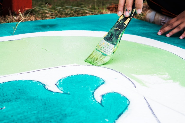 創造芸術のための紙に描くブラシで風景の水彩抽象を描くアジア学生アーティストの手