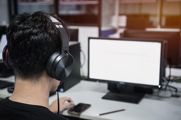 Азиатский студент молодой человек в наушниках слушает