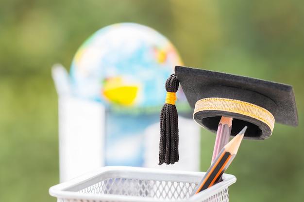 卒業研究または教育知識は力の概念です:卒業キャップバスケットに鉛筆を置く