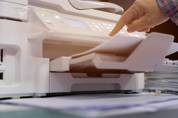 Сотрудник нажимает кнопку на панели принтера