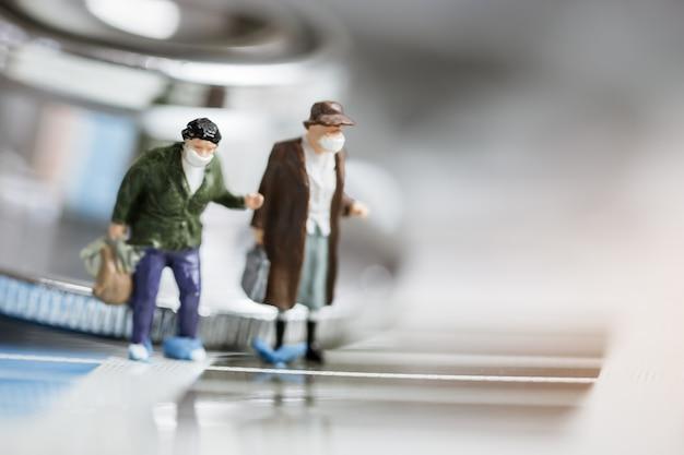 コロナウイルスアウトブレイクウイルスのコンセプトミニフィギュアの人やサージカルマスクを身に着けている観光客の男性