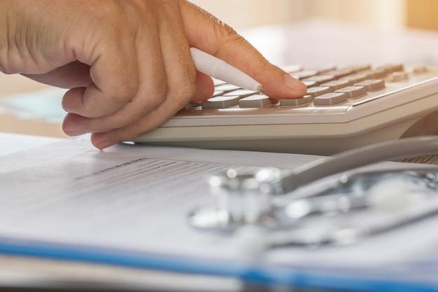Врач здравоохранения рассчитывает на электронный калькулятор со стетоскопом