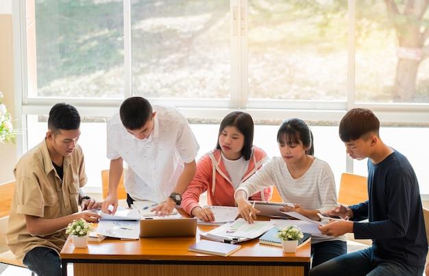Азиатский колледж группы студентов, используя ноутбук