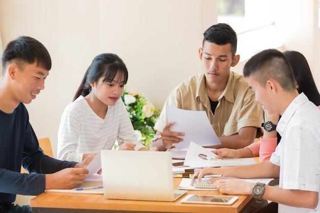Азиатский колледж группы студентов, используя ноутбук, изучая вместе