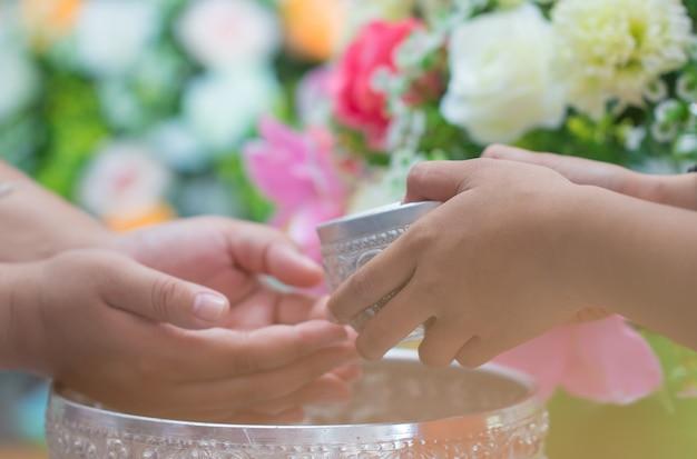 ソンクラーンタイの祭典のコンセプト:クローズアップ敬虔な長老の手に水を注ぐ