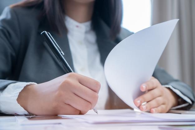Азиатская женщина-бизнесмен, проверяющая подписью заявителя, заполняя документы