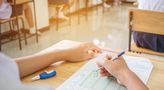 ユニフォームスクールアジアの学生は、鉛筆で答え光学フォームを書く試験を取る