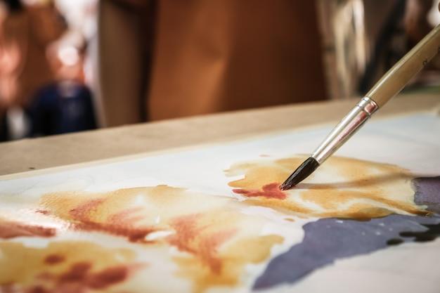 生徒の手で筆を描く紙の上に水彩画の抽象画を作成する