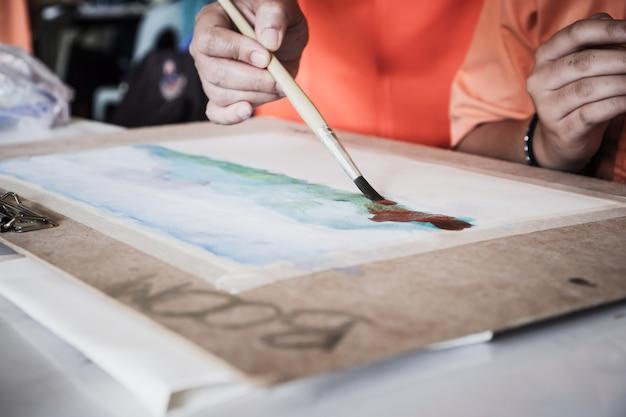 紙の上に筆を描く生徒の手絵画水彩画の抽象画