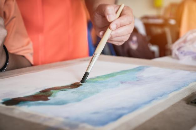 紙に筆を描く学生の手