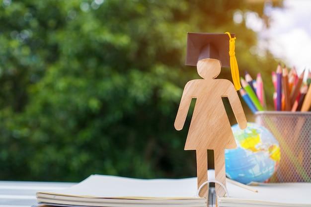 人々は開いた教科書の帽子を祝う卒業と木材を署名する