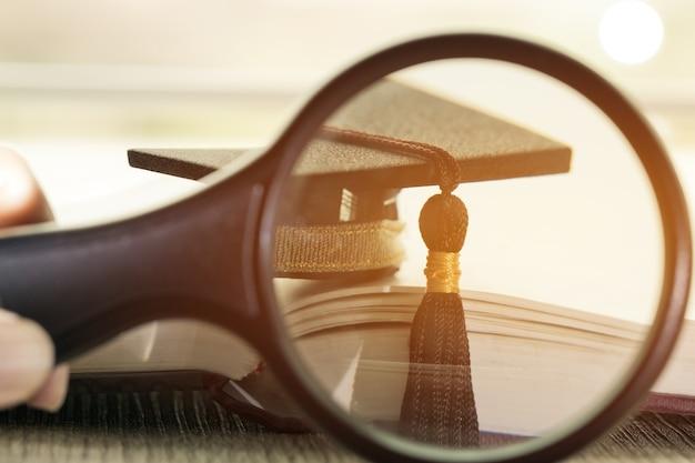 Студенческие руки держат увеличительное стекло на книжном документе
